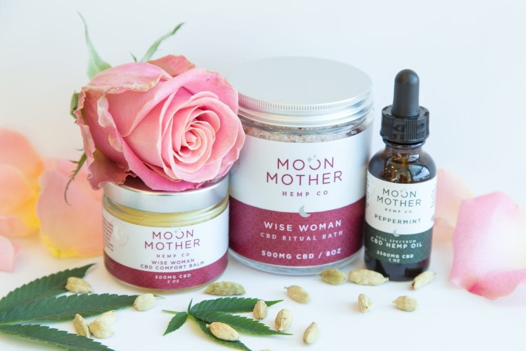 Wise Woman Moon Time CBD Box with balm, bath salts and tincture surrounded by herbs